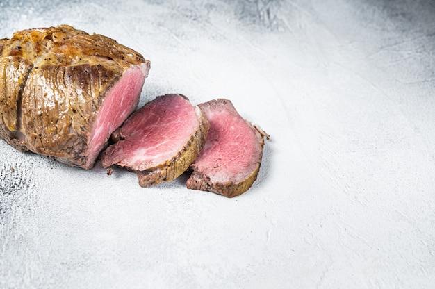 식탁에 구운 쇠고기 고기 필레. 흰 바탕. 평면도. 공간을 복사합니다.
