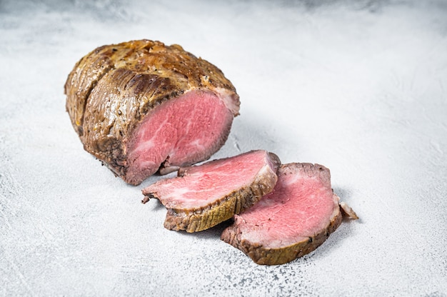 Филе мяса ростбифа на кухонном столе. белый