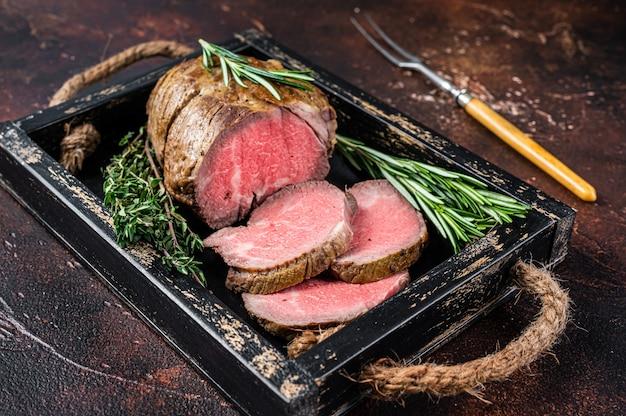 로스트 비프는 허브와 함께 나무 쟁반에 등심 고기를 둥글게 만듭니다. 어두운