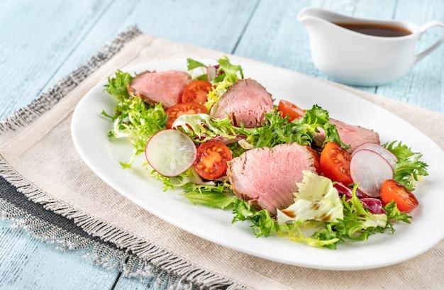 Салат с ростбифом на сервировочной тарелке
