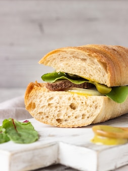 Roast beef sandwich with salad, onion and cukes and mustard sauce.