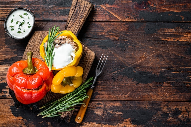 Жареный перец болгарский, фаршированный говядиной, рисом и овощами на деревянной доске. темный деревянный фон. вид сверху. скопируйте пространство.