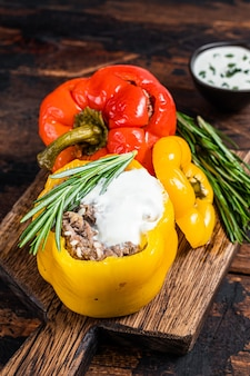 Roast bell pepper stuffed with beef meat, rice and vegetables on a wooden board. dark wooden background. top view.