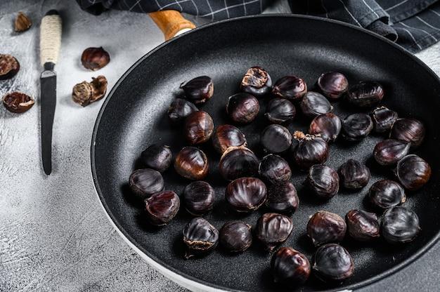 木製のテーブルの上の鍋で栗をローストします。上面図。
