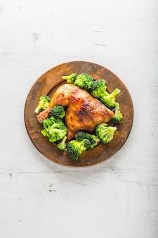 Жареная куриная ножка. куриная жареная ножка с брокколи на столе.