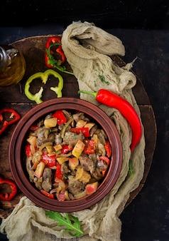 木製の背景に野菜と鶏レバーをローストします。平干し。上面図