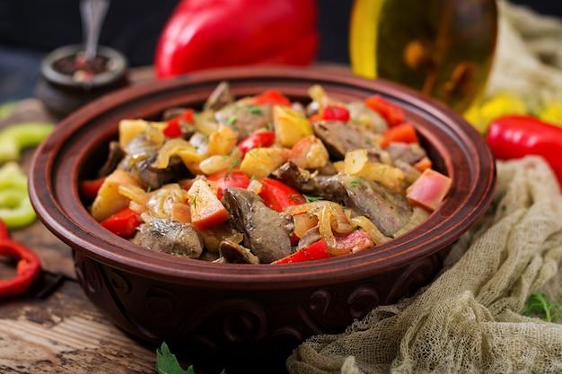 木製の背景に野菜と鶏レバーをローストします。