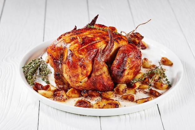 마흔 정향의 마늘을 곁들인 로스트 치킨, 흰색 플래터에 40 정향 치킨, 나무 테이블에, 프랑스 요리