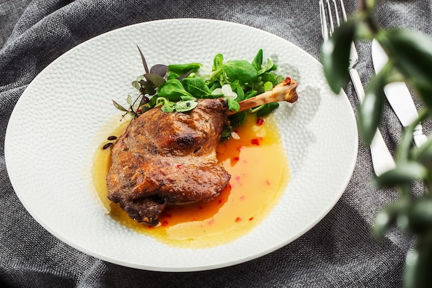 Жареная утиная ножка с соусом из манго, салатом и перцем чили на белой тарелке