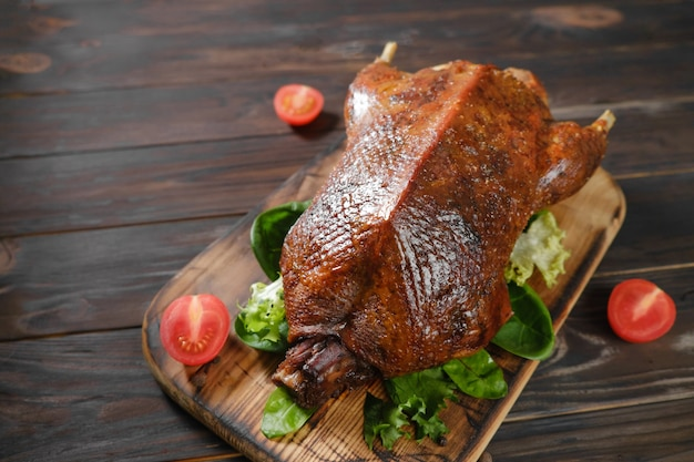 Roast duck and vegetables on a dark wooden board