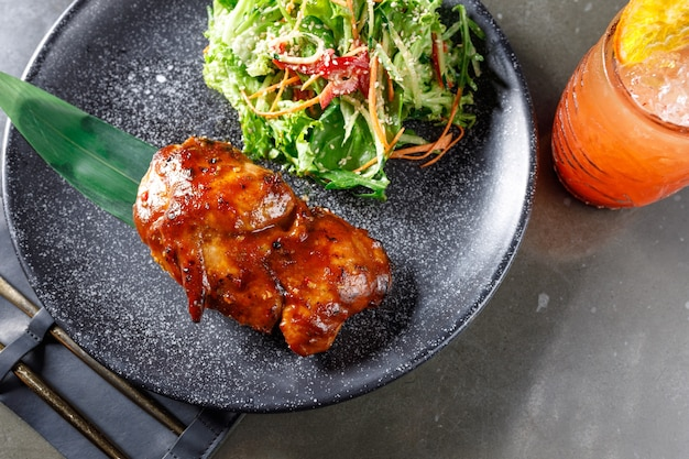 Roast duck with salad on a black plate