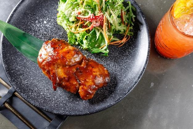 Жареная утка с салатом на черной тарелке