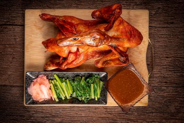 古い木製のテーブルの上にソースと野菜を添えた鴨のロースト
