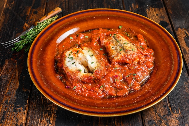 Roast hake white fish fillet with tomato sauce in a plate. dark background. top view.