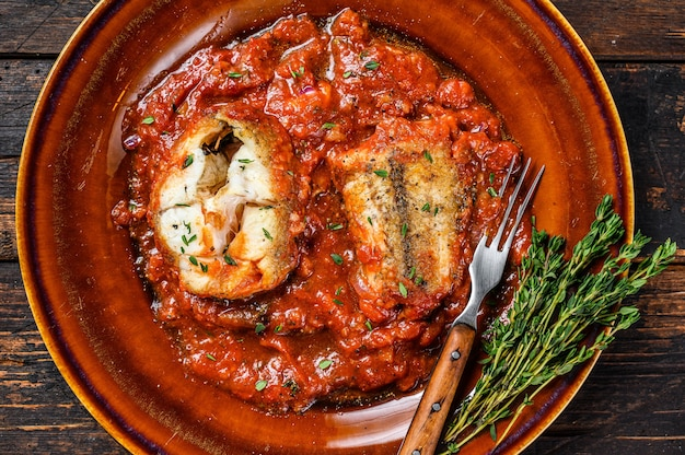 Roast hake white fish fillet with tomato sauce in a plate.   top view.