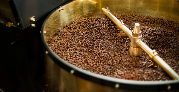 Roast machine. the freshly roasted coffee beans from a coffee roaster being poured into the cooling cylinder.