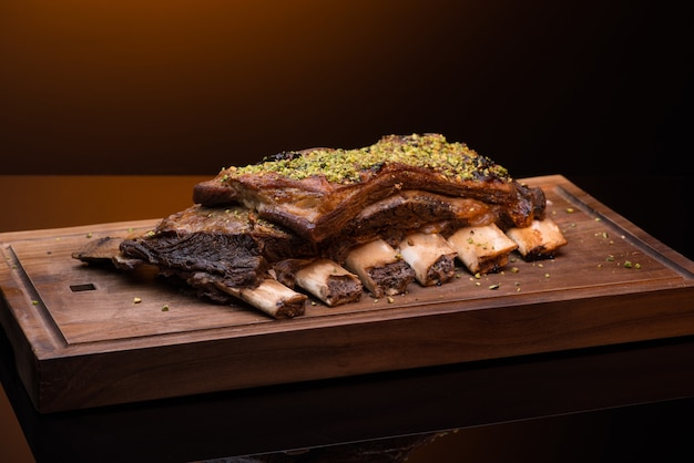 Roast meat with bone on a wooden tray, dark background, isolated