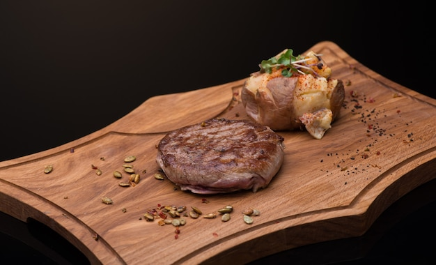 Roast meat on a wooden tray, dark background, isolated
