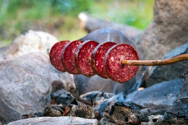 スモークソーセージを火で焼く。スライスしたソーセージ。棒に刺したソーセージ。田舎での速い夕食キャンプ。小さなキャンプファイヤー。屋外の直火でソーセージを焼く。