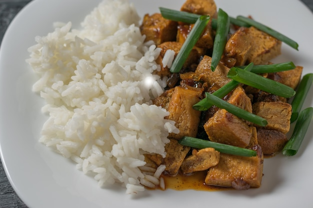 Жарьте сыр тофу с зеленым луком и рисом на белой тарелке. вегетарианское азиатское блюдо.