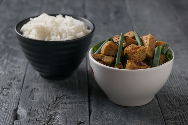 Roast tofu in a white bowl and rice in a black bowl on a wooden table. vegetarian asian dish.