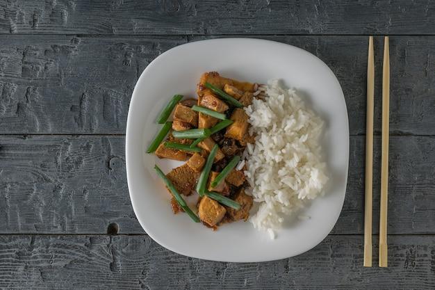 Жареный тофу с рисом и соевым соусом на столе. плоская планировка. вегетарианское азиатское блюдо.