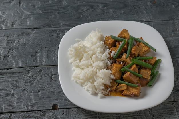 Жареный тофу с рисом и соевым соусом на столе. вегетарианское азиатское блюдо. вид сверху.