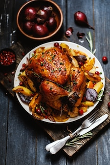 Жареный цыпленок целиком с жареными овощами на тарелке на столе
