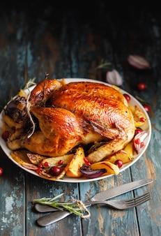 テーブルの上の皿にロースト野菜を添えて鶏肉全体をローストする