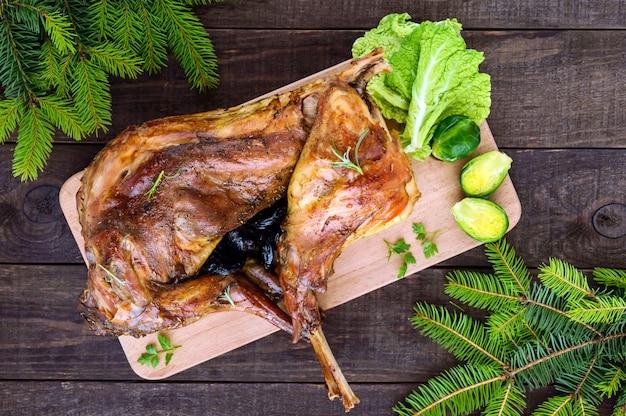 Запекать целого кролика, фаршированного черносливом, на деревянной доске с запеченной морковью и брюссельской капустой.