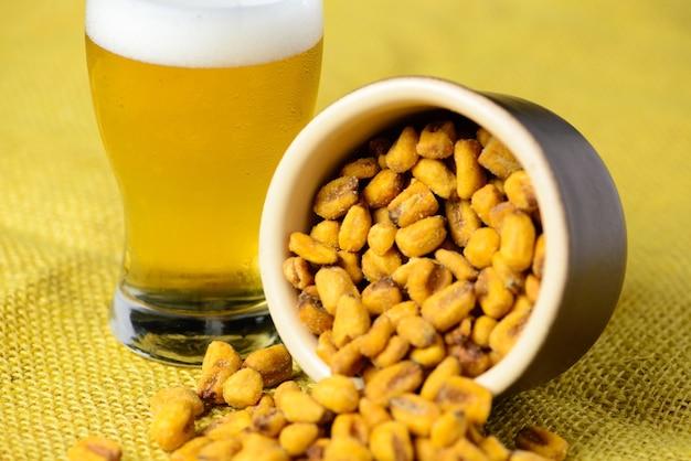 도자기 냄비에 구운 소금에 절인 옥수수와 노란 황마와 시원한 맥주 한 잔