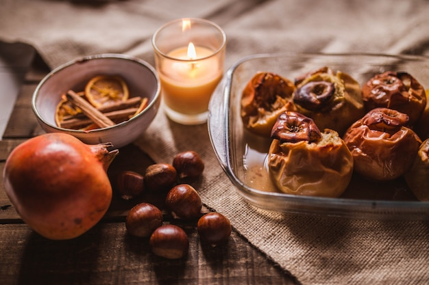Roasted apples in a glass tray with chestnuts, candle, cinnamon, orange and pomegranate