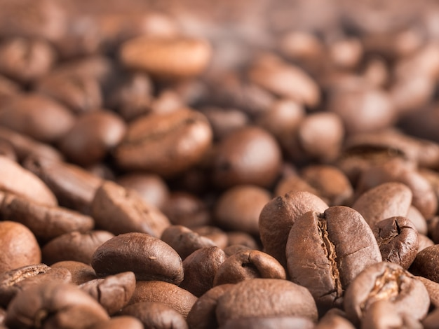 Обжаренные кофейные зерна арабика с выходящим из них паром после обжарки.