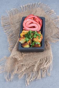 Pancetta arrosto e patate fritte sul piatto di legno nero.