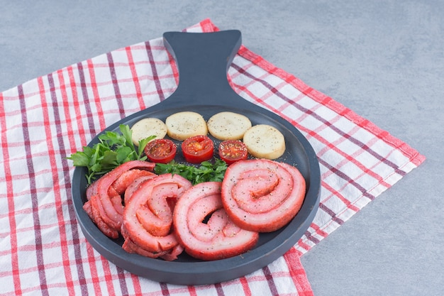 Roasted bacon with vegetables on frying pan.