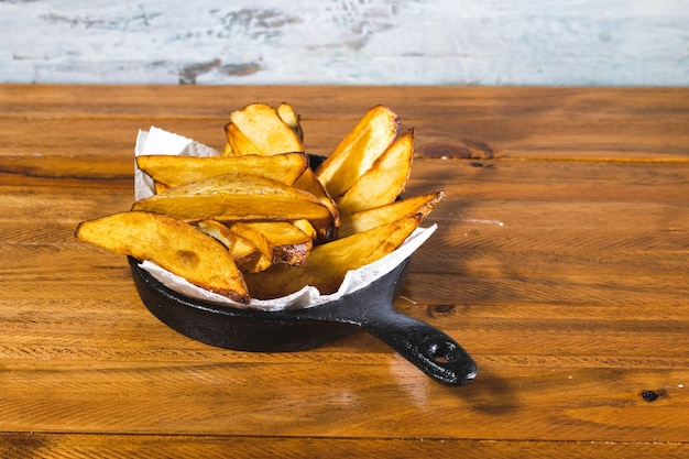 Roasted or baked potatoes in a black iron pan on wooden table.