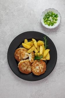 Жареный, запеченный картофель с фрикадельками из куриного котлета со свежим зеленым луком и розмарином на светло-серой поверхности