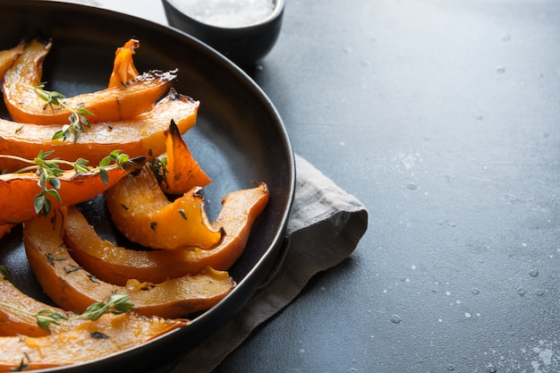 Roasted, baked pumpkin with addition aromatic thyme and salt. healthy vegan food.