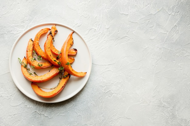 Roasted, baked pumpkin with thyme and salt. healthy vegan food.