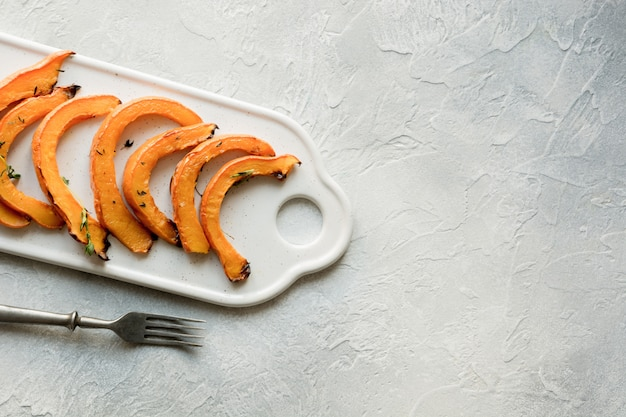 Roasted and baked pumpkin with thyme on white chopping board. healthy vegan food.