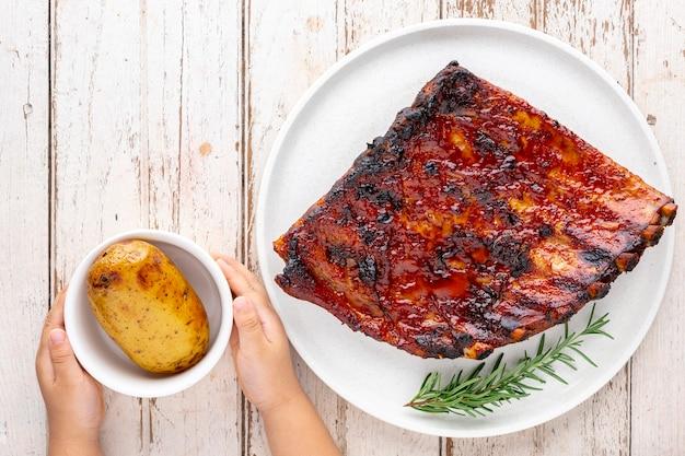 Жареные свиные ребрышки барбекю с медом, орегано и розмарином в простой белой керамической тарелке рядом с запеченным картофелем с детскими руками на белом фоне текстуры старого дерева, вид сверху