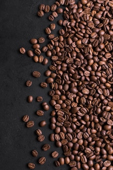 Roasted beans of tasteful coffee on black background