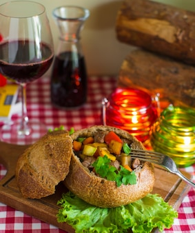 Roasted beef dish with potatoes, carrot and pepper in bread bowl