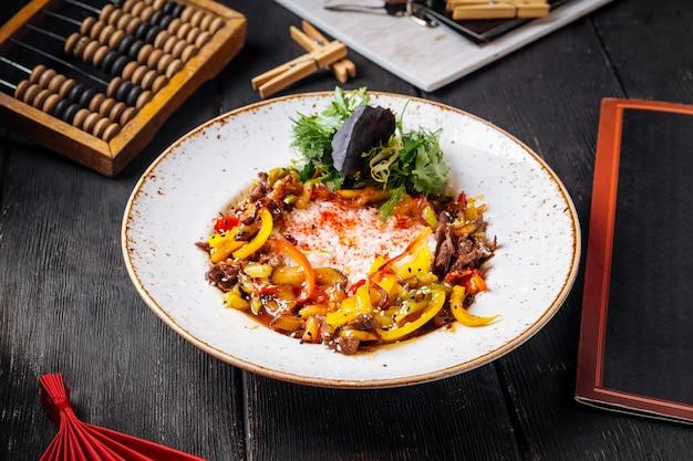 Жареное мясо говядины с болгарским перцем и рисом на черном деревянном столе