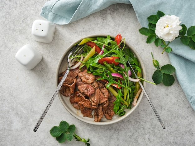 Roasted beef with fresh vegetables and herbs salad.