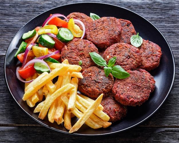 감자 튀김, 토마토 오이의 신선한 샐러드, 신선한 바질과 붉은 양파와 함께 구운 비트 버거 버거는 어두운 나무 테이블에 검은 접시에 제공, 근접