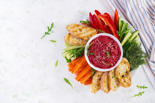 Жареный свекольный хумус с тостами и овощами. хумус из свеклы. вид сверху, сверху, копия пространства