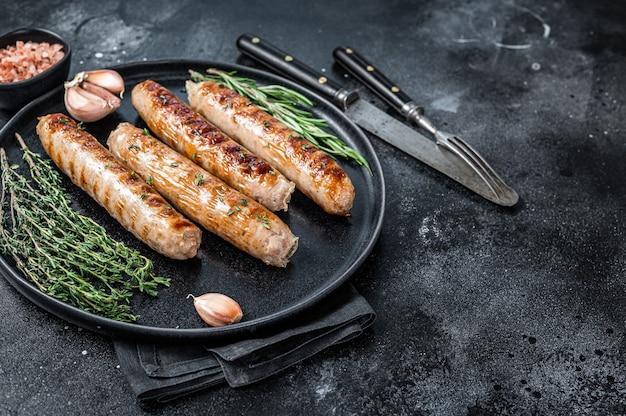 접시에 구운 bockwurst 돼지 고기 소시지. 검은 배경. 평면도. 공간을 복사합니다.