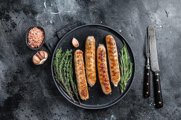 접시에 구운 bockwurst 돼지 고기 소시지. 검은 배경. 평면도.