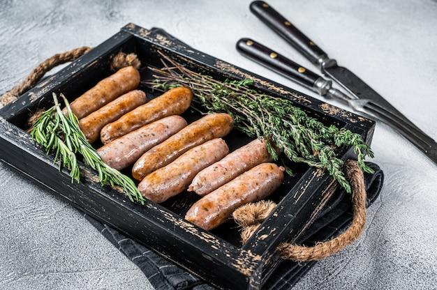 Жареные сосиски bratwurst hot dog на деревянном подносе с зеленью. вид сверху.
